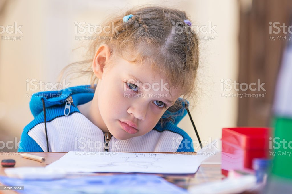 sad girl sits at a table in courtyard of house stock photo