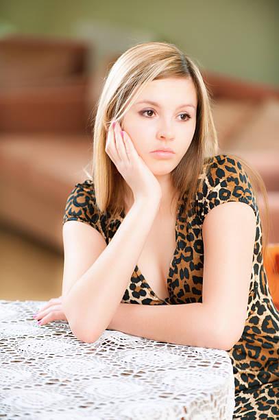 Sad girl sits at table stock photo