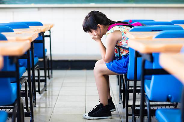 Une fille assise et triste pensant dans la salle de classe - Photo