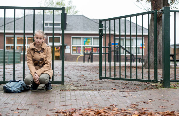 Sad girl sitting at school gate alone stock photo