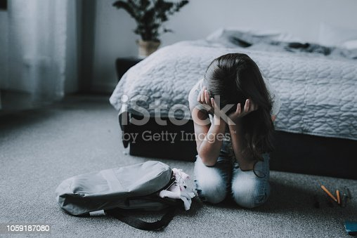 Girl Sitting on Floor in Bedroom and Crying. Portrait of Unhappy Black-Haired Child with Closed Eyes Covers Face with Hands Wearing Gray T-Shirt Sits Near Backpack next to Bed in Modern Apartment
