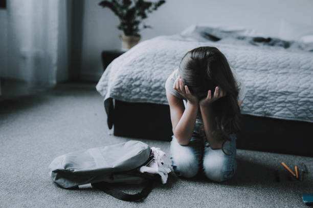 Sad Girl Sitting on Floor in Bedroom and Crying stock photo