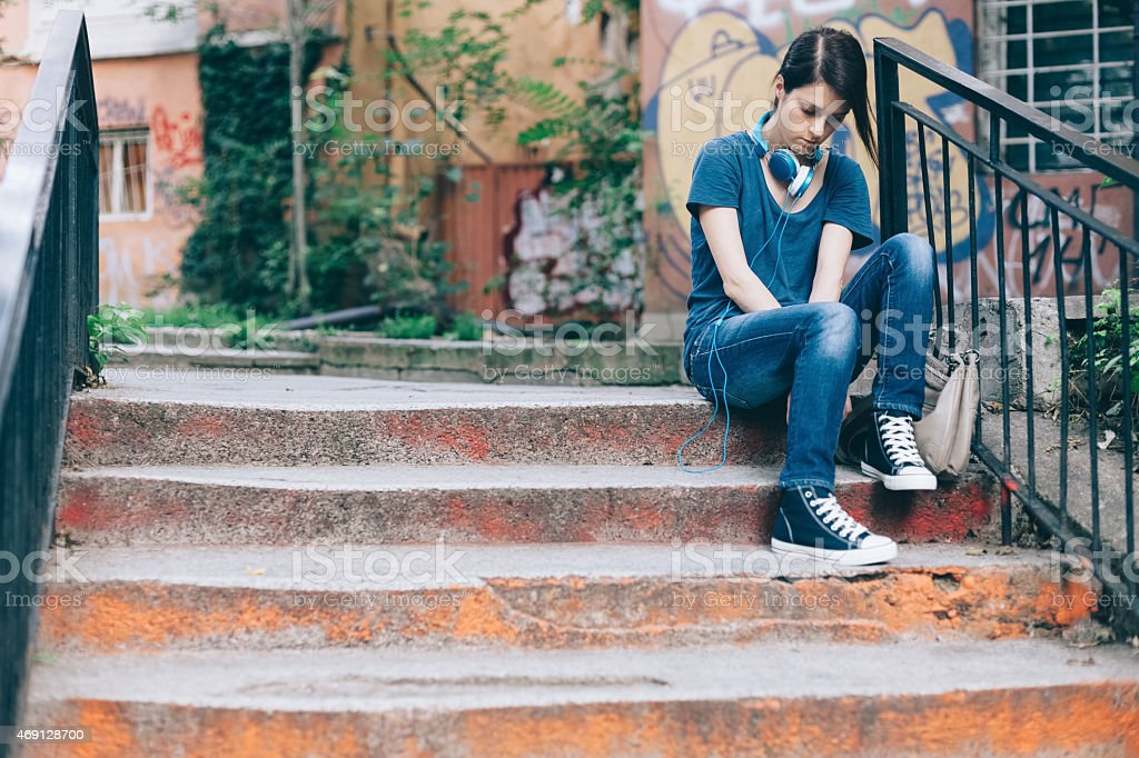 Sad girl sitting on ground stock photo