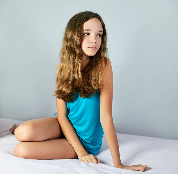 sad girl sitting on the bed and looking away. square - tween models stock photos and pictures