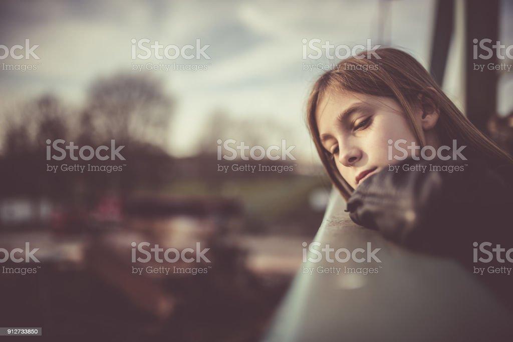 Sad girl standing on the bridge stock photo