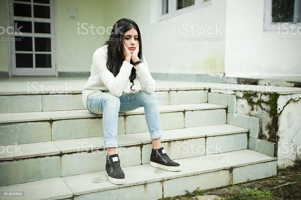 Sad girl thinking and sitting on steps, holding her head. stock photo