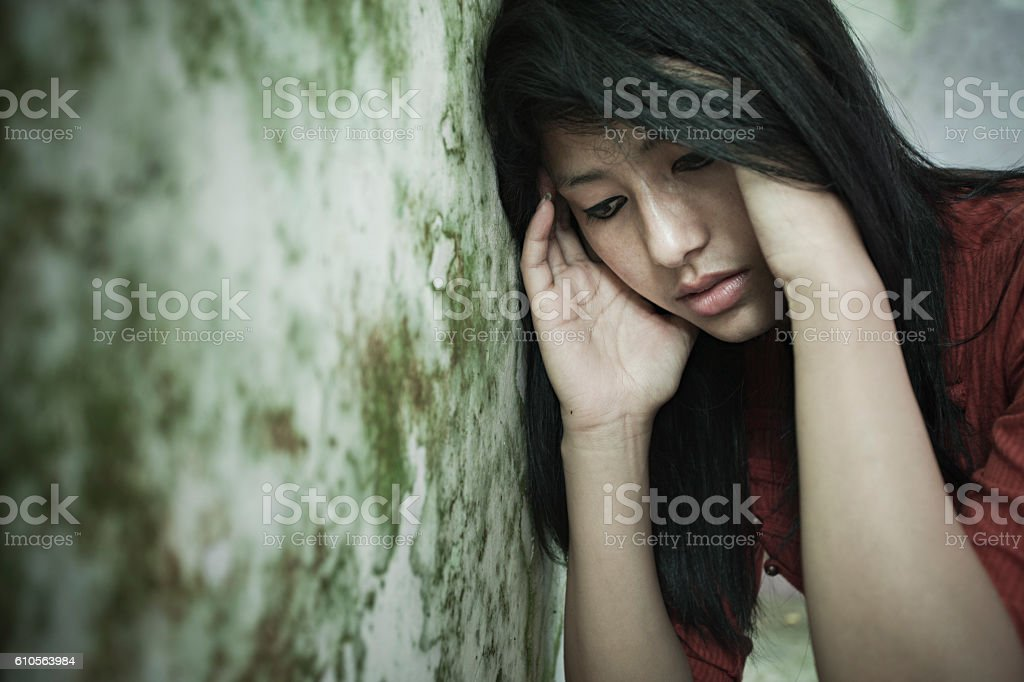 Sad girl thinking, looking down while leaning against dirty wall. stock photo
