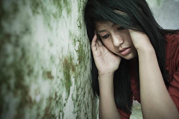 sad girl thinking, looking down while leaning against dirty wall. - migräne vorbeugen stock-fotos und bilder