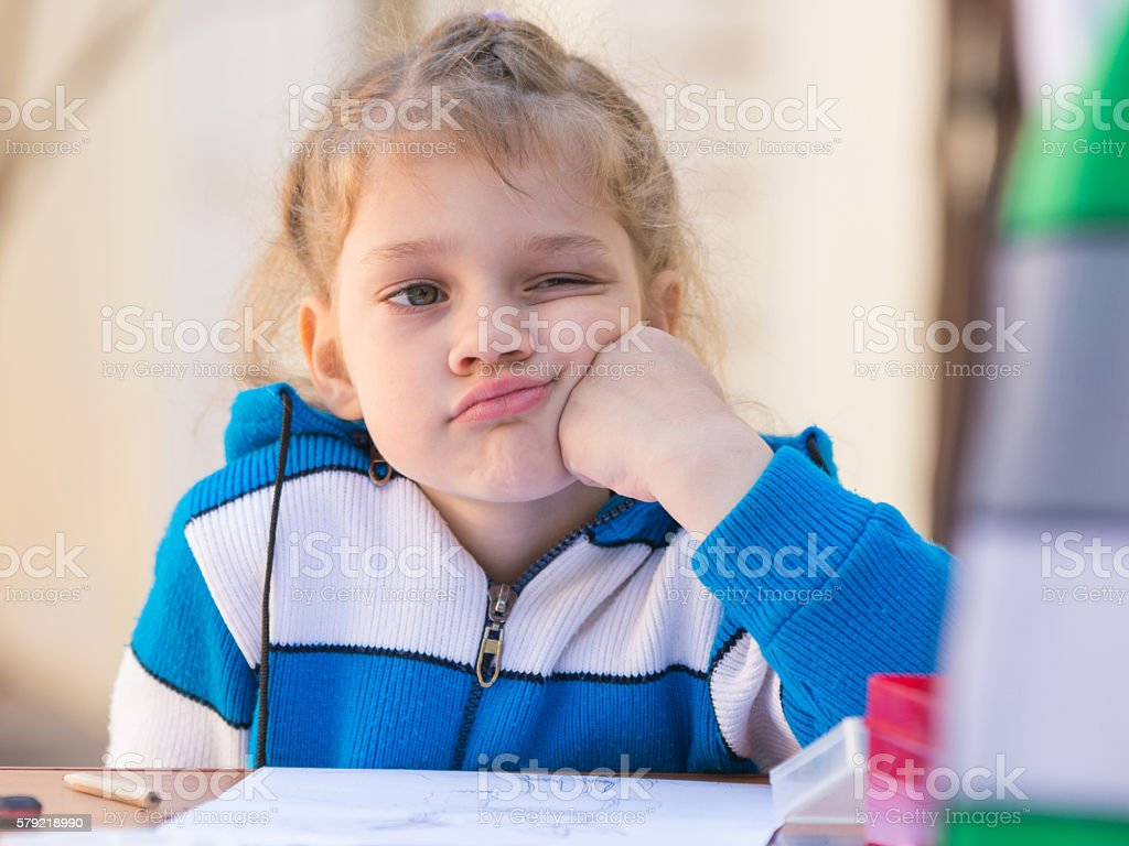 Sad girl thought doing drawing at a table in yard stock photo