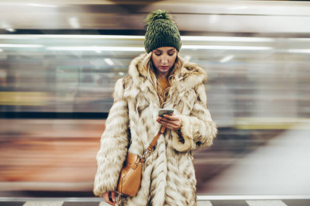 Sad girl using her phone while standing on a subway platform Depressed young girl uisng her phone while waiting for her traing on the subway subway platform stock pictures, royalty-free photos & images