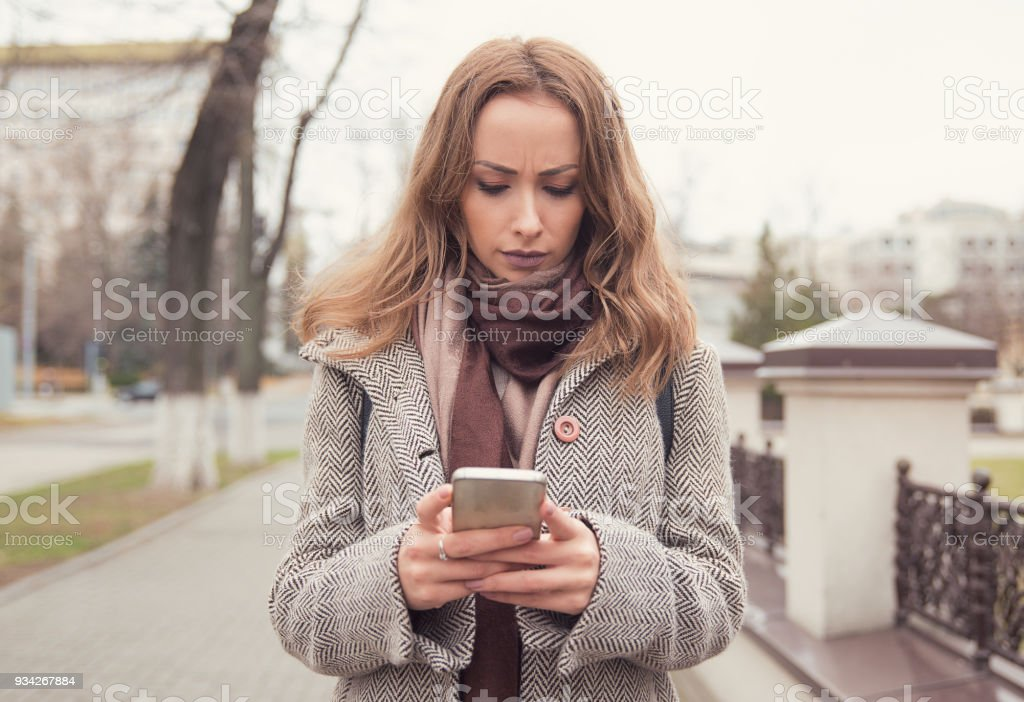 Sad girl using phone on street Young angry woman in doubt wearing coat and using smartphone on urban background. Adult Stock Photo