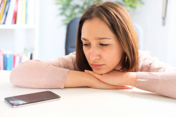 Sad girl waiting for boyfriend smartphone message stock photo