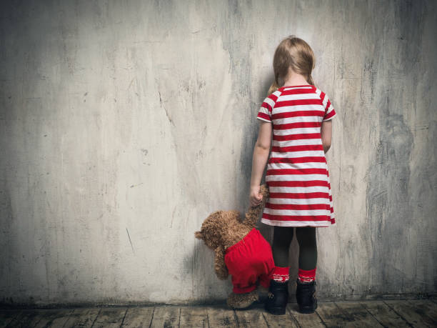 Sad girl with a toy bear standing back in the background of the textured walls. The concept of children's resentment, the complexity of education, the child's behavior stock photo