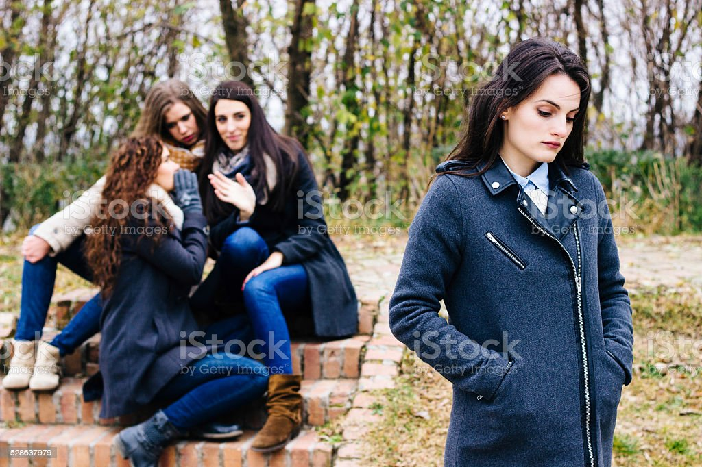 Sad girl with friends gossiping stock photo