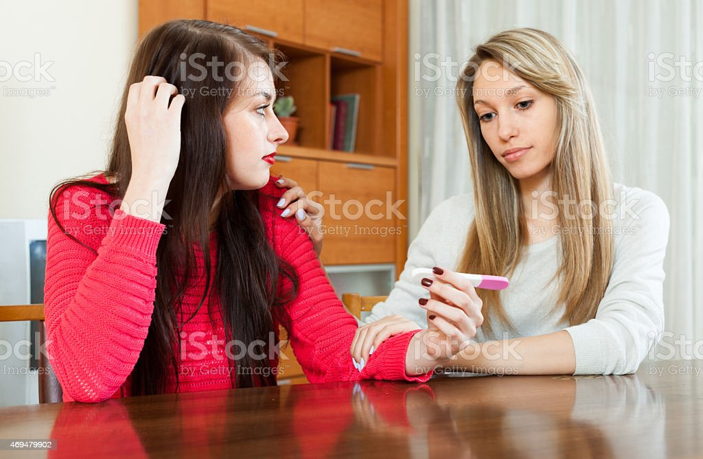 Sad girl with pregnancy test, girlfriend consoling her stock photo