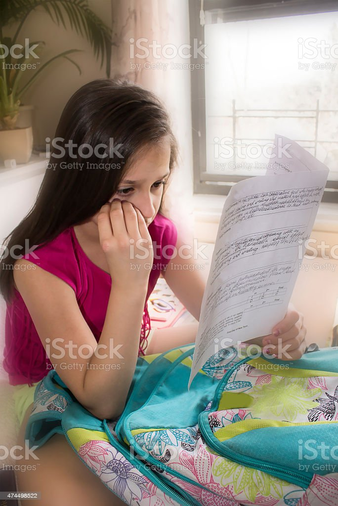 Sad girl with report card stock photo