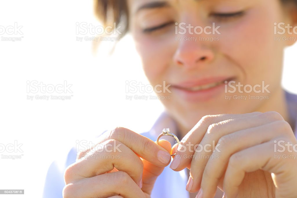Sad girlfriend looking her engagement ring stock photo