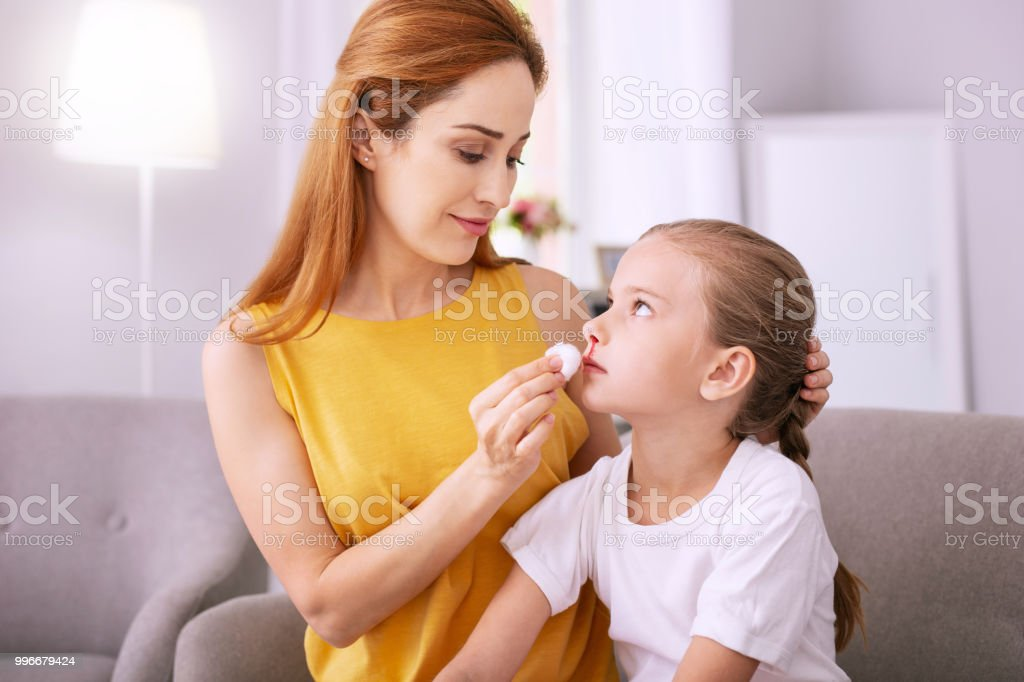 Sad gloomy girl sitting together with her mom stock photo
