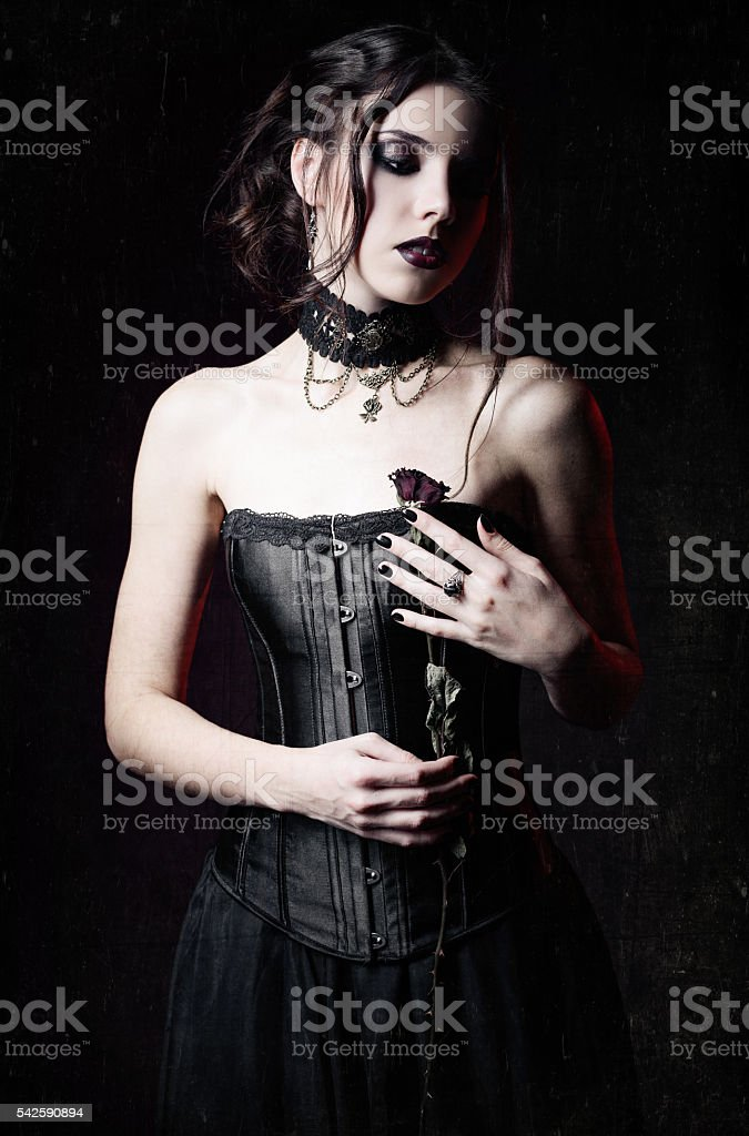 Sad goth girl holding withered rose. Grunge texture effect stock photo