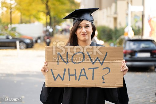 Sad Graduate Student Standing With Now What Placard On Street
