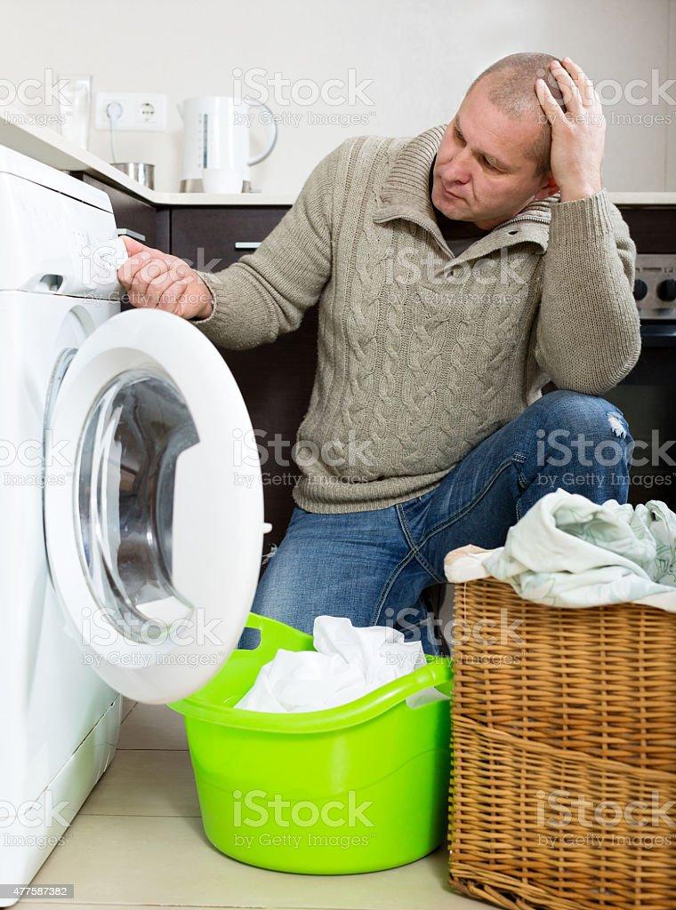 Sad guy using washing machine stock photo