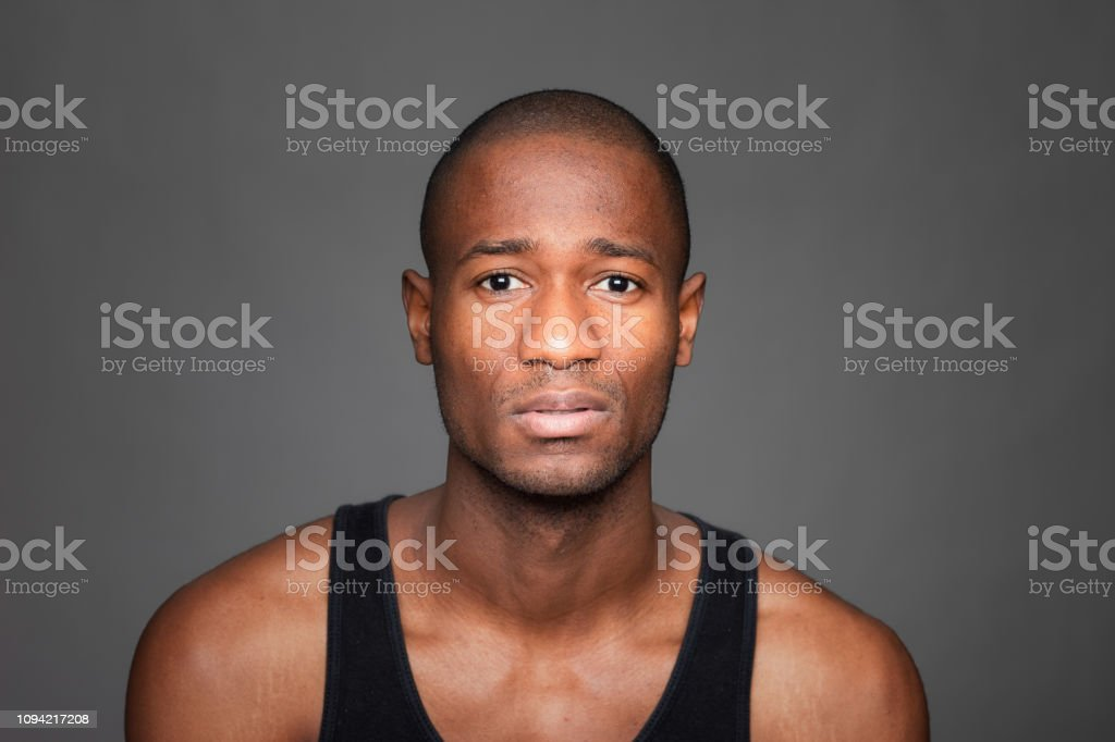 Sad Haitian man on dark background. He is wearing a tank top and...