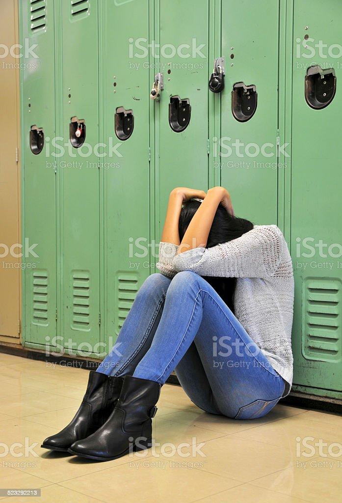 Sad High School Girl Sitting Against Locker Stock Photo -3594