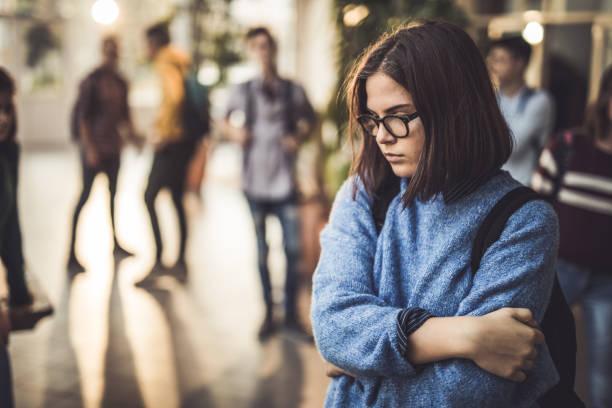 traurige gymnasiasten fühlen sich einsam in einem flur. - jugendalter stock-fotos und bilder
