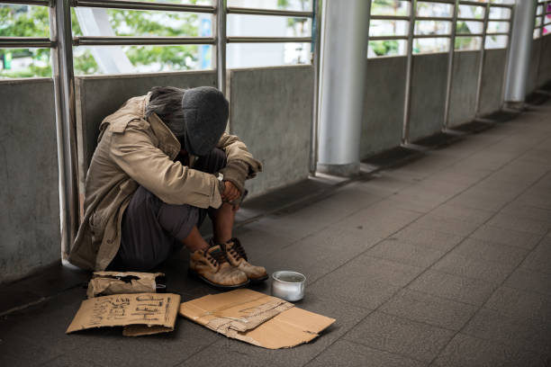 Sad Homeless old man in city Sad Homeless old man or beggar head down and sit on city walk. Poverty with depression feeling in winter. Social issue concept. homelessness stock pictures, royalty-free photos & images