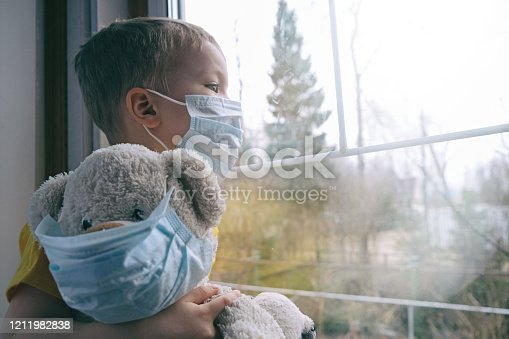 Sad illness child on home quarantine. Boy and his teddy bear both in protective medical masks sits on windowsill and looks out window. Virus protection, coronavirus pandemic, prevention epidemic.