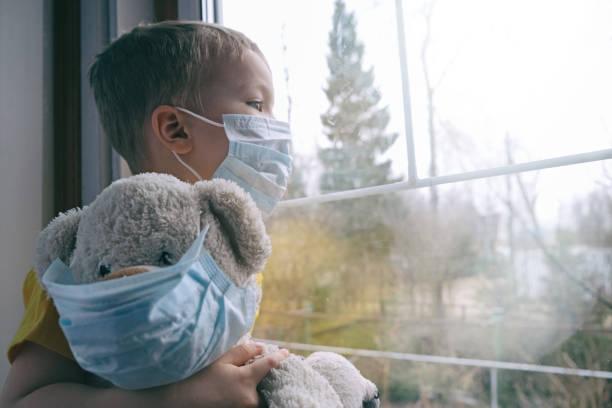 triste malattia bambino in quarantena a casa. il ragazzo e il suo orsacchiotto entrambi in maschere mediche protettive si siede sul davanzale della finestra e guarda fuori dalla finestra. protezione dai virus, pandemia di coronavirus, epidemia di prevenzio - bambino foto e immagini stock