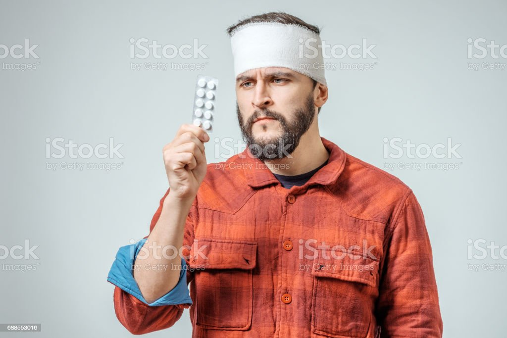 Sad injured bandaged man with pills over gray background stock photo