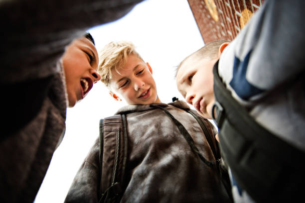 sad intimidation moment Elementary Age Bullying in Schoolyard stock photo