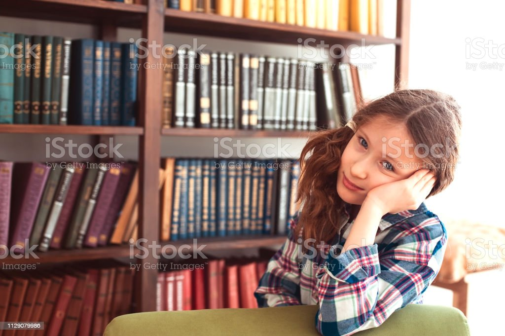 sad kid girl posing near book shelf at home. Teaching kids to love...