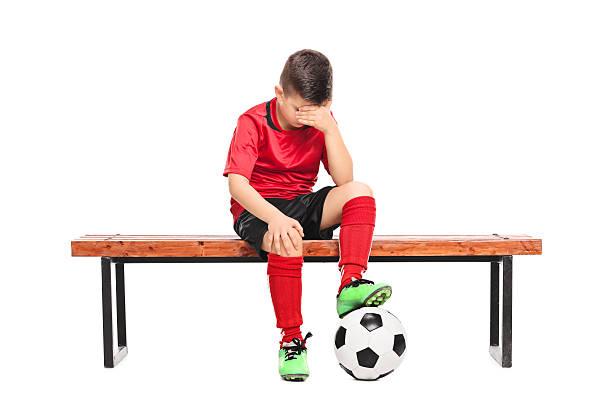 traurigen kind beim fußball uniform sitzt auf einer bank - sitzbank schuhe stock-fotos und bilder