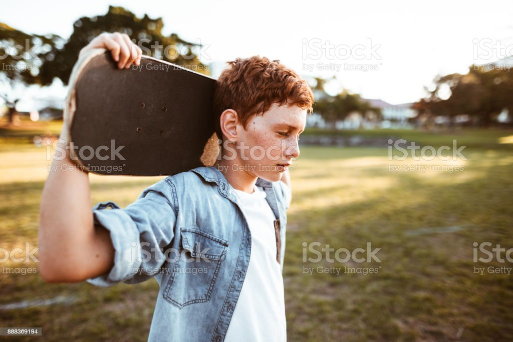 sad kid with the skateboard on the shoulder stock photo