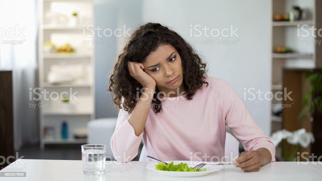 Traurige Frau vor grünem Salat-Teller und Glas Wasser am Tisch, Gewichtsverlust – Foto