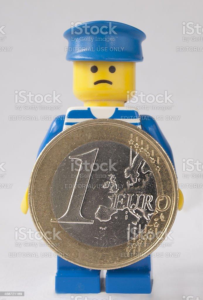 Sad LEGO man holding up One Euro coin royalty-free stock photo