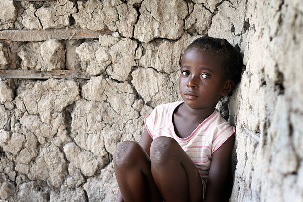 Sad little African girl, sitting against a wall stock photo