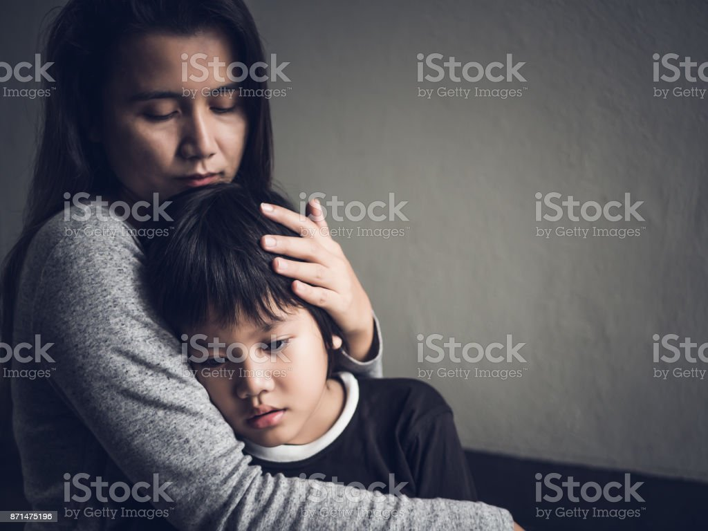 Sad little boy being hugged by his mother at home. Parenthood, Love and togetherness concept. stock photo