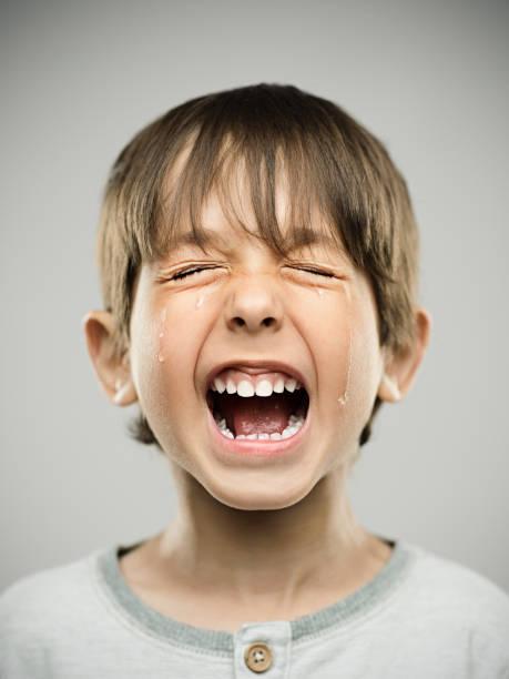 Sad little boy crying loudly stock photo