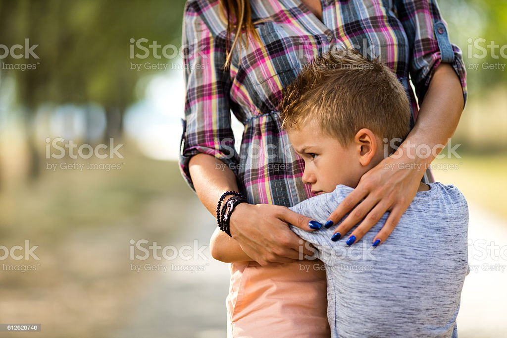 Sad little boy embracing his unrecognizable mother in nature. stock photo