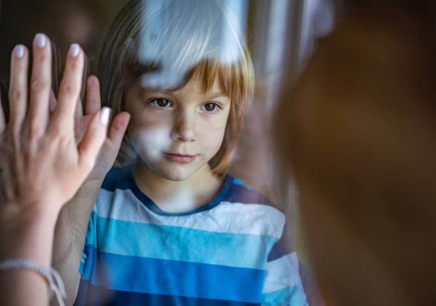 sad little boy in home during epidemic coronavirus - hand on glass covid foto e immagini stock