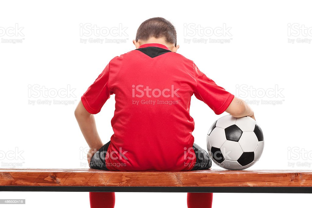 Sad little boy in red soccer jersey seated on bench stock photo