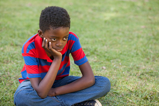 Sad little boy in the park Sad little boy in the park on a sunny day puckering stock pictures, royalty-free photos & images