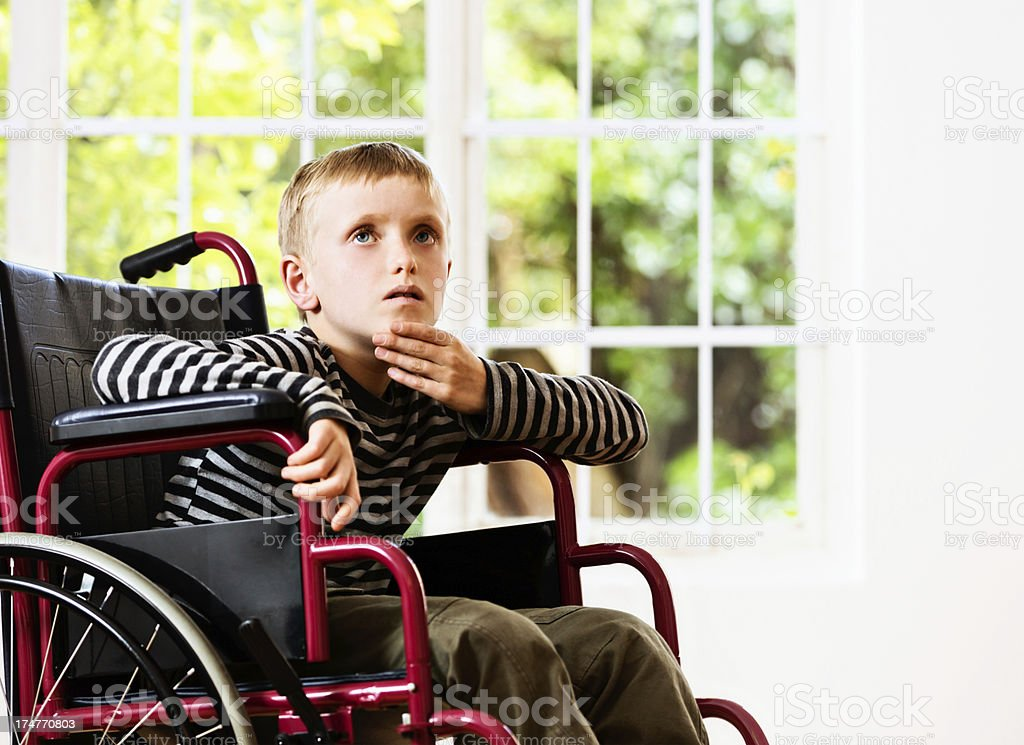Sad little boy in wheelchair looks up, listening to someone stock photo