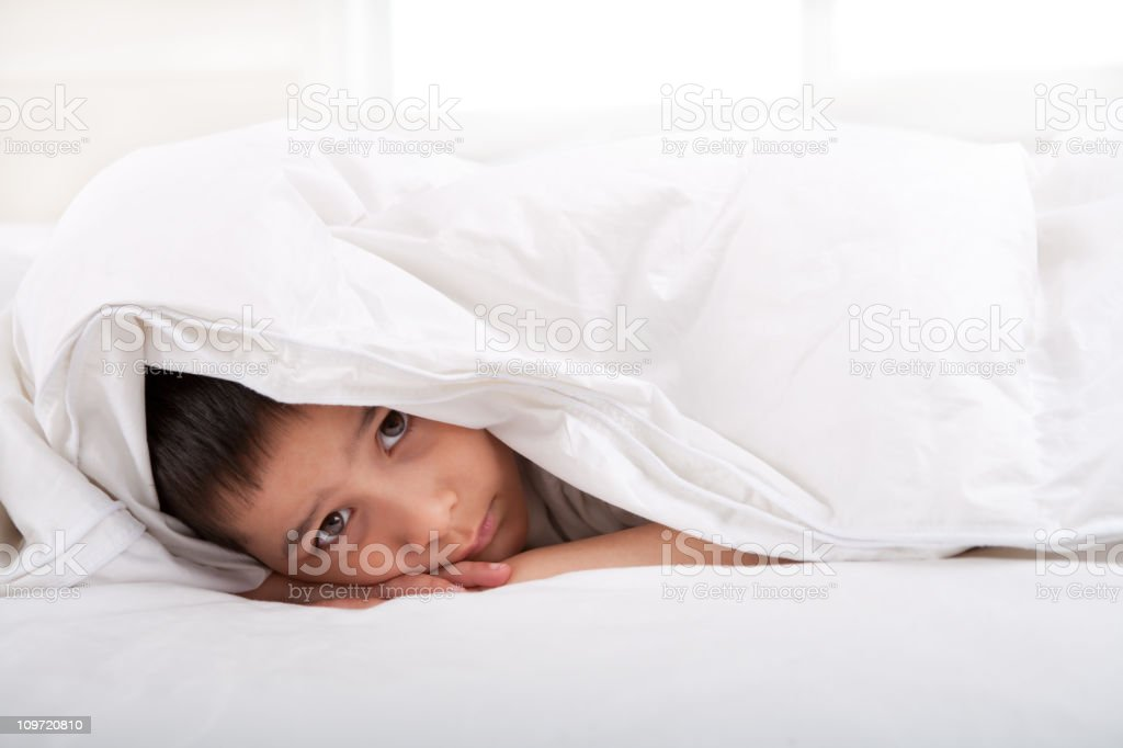 Sad little boy laying under blanket royalty-free stock photo