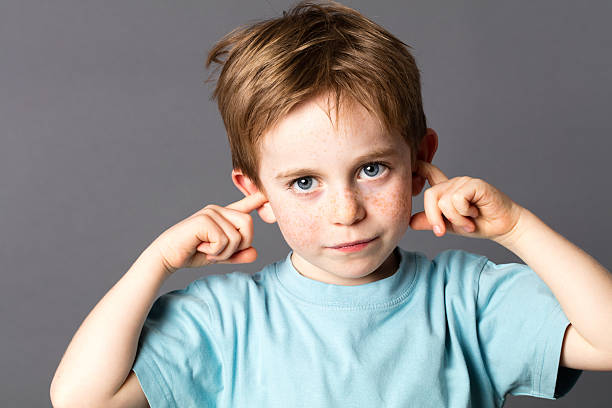 sad little boy not willing to listen to domestic violence sad little boy with blue eyes and freckles not willing to listen to domestic violence or parent relationship problems, covering his closed ears, grey background hands covering ears stock pictures, royalty-free photos & images