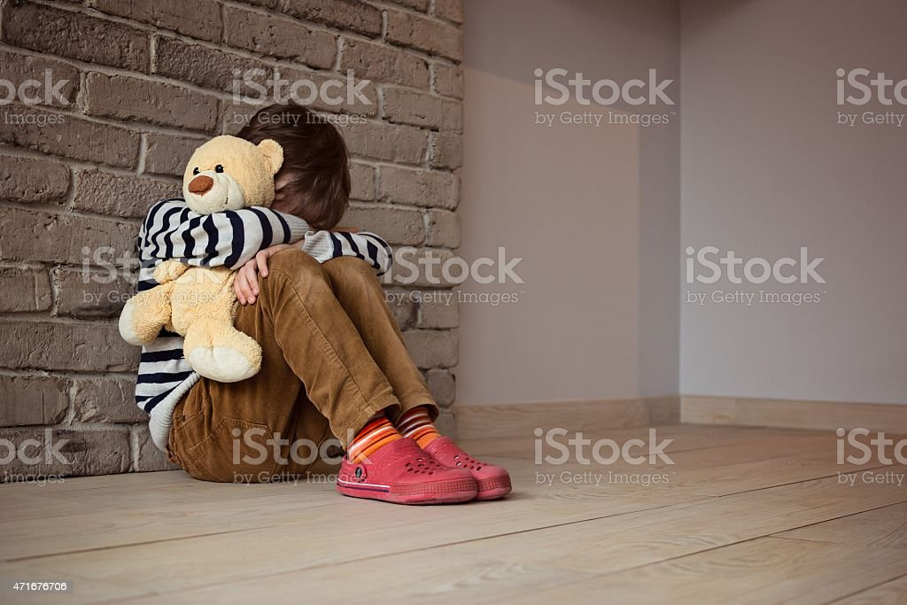 Sad little boy sitting against the wall in despair stock photo