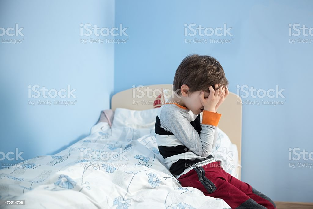 Sad little boy sitting on the edge of his bed. stock photo